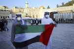 Emirati singer Walid Aljasim, left, and an unidentified companion pose for a photo with the flag of the United Arab Emirates during their visit in Jerusalem, next to the Western Wall the holiest site where Jews can pray, Thursday, Dec. 3, 2020. (AP Photo/Mahmoud Illean)