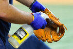 A glove is disinfected by Houston Astros batboy Chase Wornell during a baseball practice practice Tuesday, July 7, 2020, in Houston. (AP Photo/David J. Phillip)