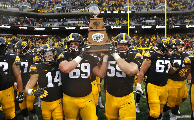 Iowa's Kyle Groeneweg (14), Keegan Render (69) and Ross Reynolds (59) carry the Heroes Trophy off the field after defeating Nebraska 31-28 in an NCAA college football game, Friday, Nov. 23, 2018, in Iowa City, Iowa. (AP Photo/Charlie Neibergall)