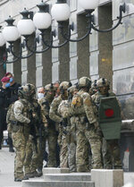 Ukraine's special police prepare to storm a city bank in Kyiv, Ukraine, Monday, Aug. 3, 2020, after a man has threatened to blow up an explosive device inside the bank. The man, identified as Sukhrob Karimov, a 32-year-old citizen of the Central Asian nation of Uzbekistan, entered a bank office in Kyiv and said he had explosives in his backpack. He let bank clerks go and demanded that the authorities invite journalists so that he could make a statement. (AP Photo/Efrem Lukatsky)