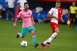Barcelona's Lionel Messi, left, vies for the ball with Girona's Gumbau during the pre-season friendly soccer match between Barcelona and Girona at the Johan Cruyff Stadium in Barcelona, Spain, Wednesday, Sept. 16, 2020. (AP Photo/Joan Monfort)