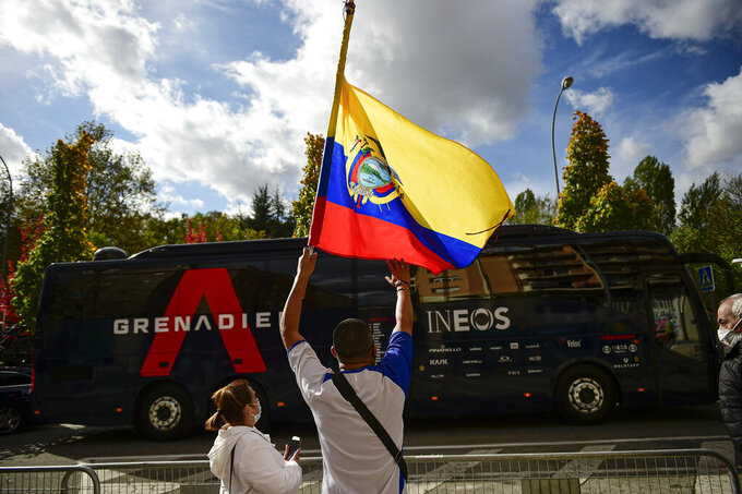 Ecuadorian fans of Richard Carapaz, waves national flag in front of the Ineos's team bus before the second stage of La Vuelta between Pamplona and Lekunberri, in Pamplona, northern Spain, Wednesday, Oct. 21, 2020. (AP Photo/Alvaro Barrientos)