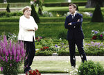 French President Emmanuel Macron talks to German Chancellor Angela Merkel during a meeting at Meseberg Castle, the German government's guest house in Meseberg, Germany, June 29, 2020. One of the topics of the meeting is the European reconstruction plan of 750 billion euros in the Corona crisis. (Kay Nietfeld/dpa via AP)