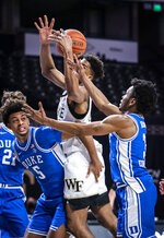 Wake Forest forward Isaiah Mucius grabs a rebound over Duke forward Jaemyn Brakefield (5) duirng an NCAA college basketball game Wednesday, Feb. 17, 2021, in Wintson-Salem, N.C. (Andrew Dye/The Winston-Salem Journal via AP, Pool)