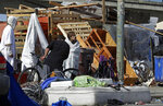 FILE - In this March 25, 2020 file photo people gather at a homeless encampment on in Oakland, Calif. City officials in Oakland, growing weary of a ballooning homeless population, approved a contentious new policy that will prohibit homeless people from setting up tents in parks or near homes, businesses, schools and some churches. (AP Photo/Ben Margot,File)