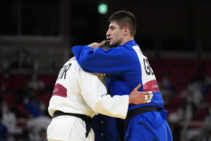 Eduard Trippel of Germany, right comforts Michael Zgank of Turkey after winning their men -90kg semifinal round against unseen, in the judo match at the 2020 Summer Olympics in Tokyo, Japan, Wednesday, July 28, 2021. (AP Photo/Vincent Thian)