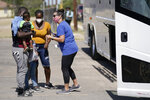 Migrants check in with a volunteer before boarding a bus to Houston at a humanitarian center after they were released from United States Border Patrol upon crossing the Rio Grande and turning themselves in seeking asylum, Wednesday, Sept. 22, 2021, in Del Rio, Texas. (AP Photo/Julio Cortez)