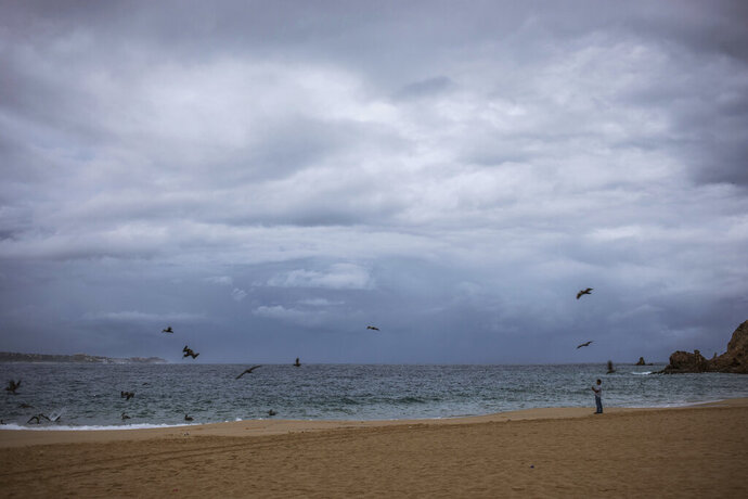A tourist walks on the beach before the expected arrival of Hurricane Lorena, in Los Cabos, Mexico, Friday, Sept. 20, 2019. Hurricane Lorena neared Mexico's resort-studded Los Cabos area Friday as owners pulled their boats from the water, tourists hunkered down in hotels, and police and soldiers went through low-lying, low-income neighborhoods urging people to evacuate. (AP Photo/Fernando Castillo)
