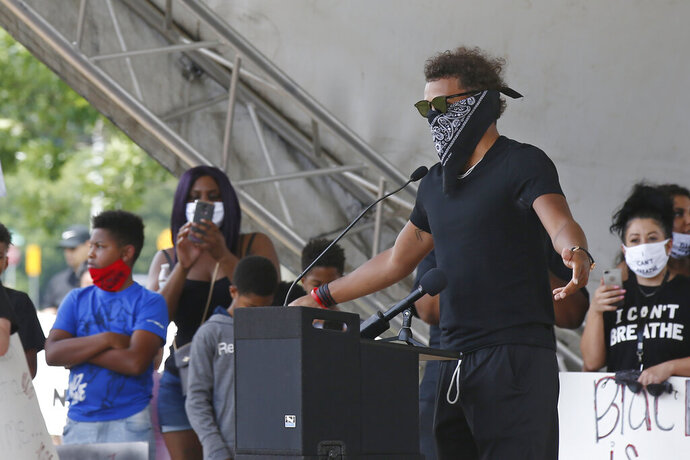 Atlanta Hawks guard Trae Young, right, speaks during a peaceful rally Monday, June 1, 2020, in his hometown of Norman, Okla., calling attention to the killing of George Floyd by Minneapolis police on May 25. (AP Photo/Sue Ogrocki)