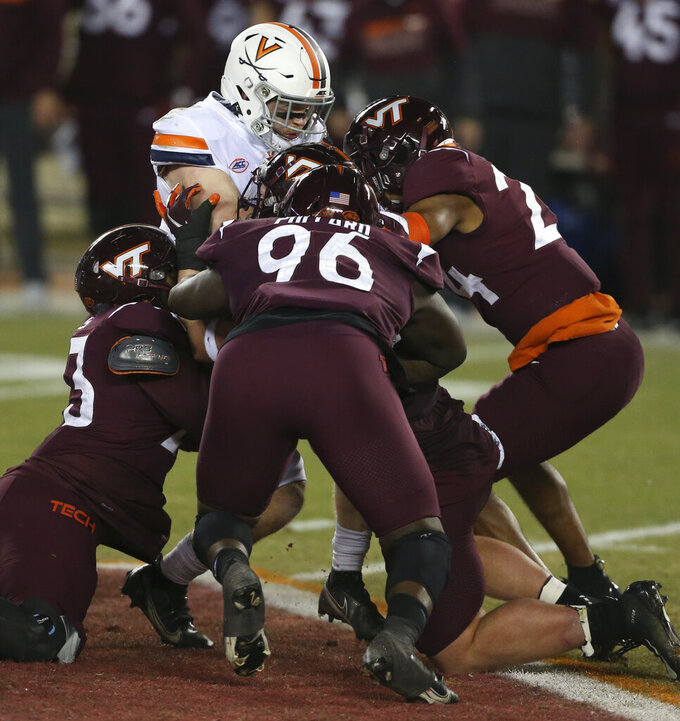 Virginia quarterback Brennan Armstrong is stopped by Virginia Tech defenders during the first half of an NCAA college football game Saturday, Dec. 12, 2020, in Blacksburg, Va. (Matt Gentry/The Roanoke Times via AP, Pool)