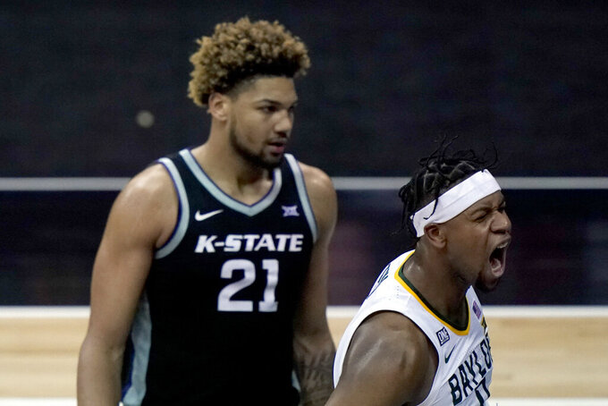 Baylor's Flo Thamba, right, celebrates after getting past Kansas State's Davion Bradford to put up a shot during the second half of an NCAA college basketball game in the second round of the Big 12 men's tournament in Kansas City, Mo., Thursday, March 11, 2021. (AP Photo/Charlie Riedel)