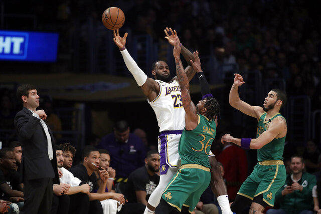 Los Angeles Lakers' LeBron James (23) is defended by Boston Celtics' Marcus Smart (36) and Jayson Tatum during the first half of an NBA basketball game Sunday, Feb. 23, 2020, in Los Angeles. (AP Photo/Marcio Jose Sanchez)