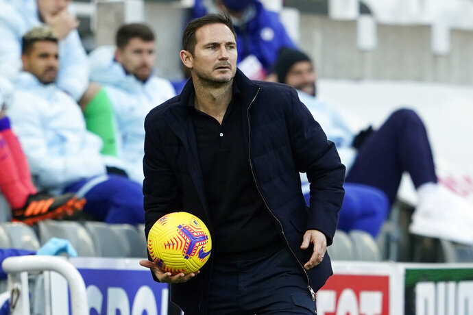 Chelsea's head coach Frank Lampard holds the ball during the English Premier League soccer match between Newcastle United v Chelsea at the St. James' Park in Newcastle, England, Saturday, Nov. 21, 2020. (Owen Humphreys/Pool via AP)