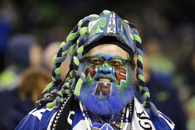 A fan painted in honor of Monday Night Football looks on before an NFL football game between the Seattle Seahawks and the Minnesota Vikings, Monday, Dec. 2, 2019, in Seattle. (AP Photo/Ted S. Warren)