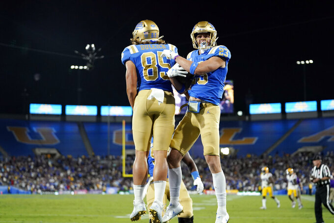 UCLA wide receiver Chase Cota, right, celebrates his touchdown catch with tight end Greg Dulcich (85) during the second half of the team's NCAA college football game against LSU on Saturday, Sept. 4, 2021, in Pasadena, Calif. (AP Photo/Marcio Jose Sanchez)