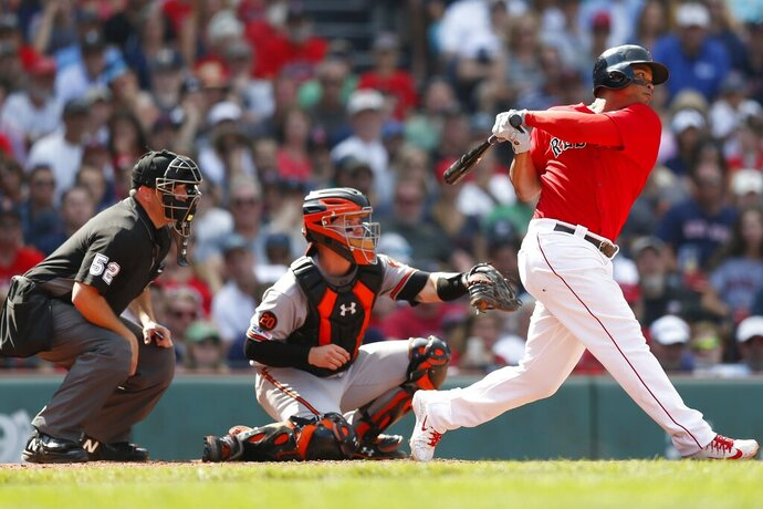 Boston Red Sox's Rafael Devers, right, follows through on an RBI double in front of Baltimore Orioles' Chance Sisco during the sixth inning of a baseball game in Boston, Sunday, Aug. 18, 2019. (AP Photo/Michael Dwyer)
