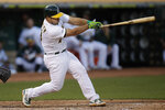 Oakland Athletics' Josh Phegley swings for an RBI single off Texas Rangers' Brock Burke during the first inning of a baseball game Saturday, Sept. 21, 2019, in Oakland, Calif. (AP Photo/Ben Margot)