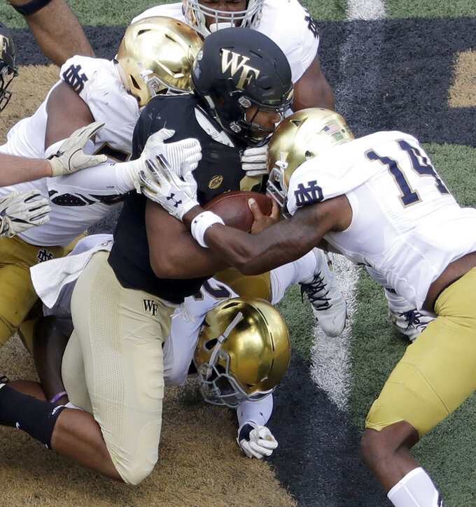 Wake Forest's Jamie Newman, center, is hit by Notre Dame's Devin Studstill (14) in the second half of an NCAA college football game in Winston-Salem, N.C., Saturday, Sept. 22, 2018. (AP Photo/Chuck Burton)