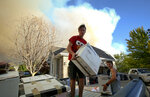 In this Thursday, Sept. 13, 2018, photo Brandon Morgan, 17, center, loads items into a truck as his friend, Carter Wilkey, 16, helps Morgan evacuate from his Elk Ridge, Utah home during a mandatory evacuation. A fast-moving Utah wildfire fanned by high-winds has more than doubled in size as it burns through dry terrain and forces evacuations of hundreds of homes, the U.S. Forest Service said Friday. (Isaac Hale/The Daily Herald via AP)