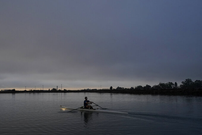 Alex Karwoski practices in the Oakland Estuary in Oakland, Calif., Thursday, Nov. 19, 2020. Nearly two dozen U.S. men's rowers signed on to keep training for another year after the Tokyo Olympics were delayed until 2021. That meant adjusting full-time jobs for many, altering wedding plans for one and maintaining apartment leases in the costly Bay Area while also dealing with different practice protocols given the coronavirus pandemic. (AP Photo/Jeff Chiu)