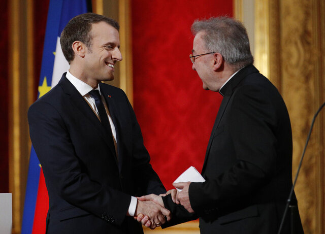 FILE - In this Jan.4, 2018 file photo, French President Emmanuel Macron, left, greets Apostolic Nuncio to France Luigi Ventura, at the Elysee Palace in Paris. Multiple men have accused Archbishop Luigi Ventura of groping and inappropriate touching, and the Vatican's former ambassador to France goes on trial Tuesday Nov. 10, 2020, for alleged sexual misconduct. (Yoan Valat, Pool via AP, File)