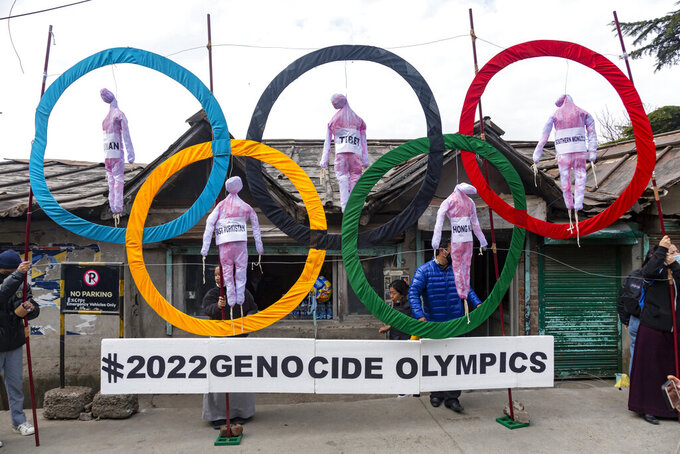 """FILE - In this Feb. 3, 2021, file photo, exile Tibetans use the Olympic rings as a prop as they hold a protest against the holding of the 2022 Beijing Winter Olympics, in Dharmsala, India. Facing the boycott-threatened Beijing Winter Olympics in just over six months, the International Olympic Committee said on Wednesday, July 28, that its only responsibility was to """"deliver the Games"""" and not to monitor human rights. (AP Photo/Ashwini Bhatia, File)"""