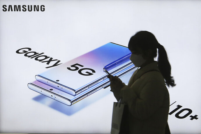A woman passes by an advertisement of Samsung Electronics' Galaxy 5G Note10+ smartphone at a subway station in Seoul, South Korea, Thursday, Jan. 30, 2020. Samsung Electronics Co. said Thursday its operating profit for the last quarter fell 33.7% from a year earlier but it predicted earnings will improve in 2020, driven by a gradually stabilizing computer chip market and increasing 5G smartphone sales. (AP Photo/Ahn Young-joon)