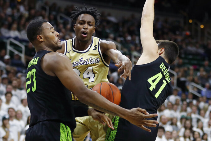 Charleston Southern guard Phlandrous Fleming Jr. (24) is defended by Michigan State forward Xavier Tillman (23) and guard Conner George (41) during the first half of an NCAA college basketball game, Monday, Nov. 18, 2019, in East Lansing, Mich. (AP Photo/Carlos Osorio)