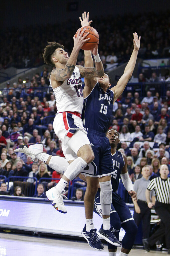Gonzaga guard Josh Perkins (13) shoots while defended by Loyola Marymount guard Joe Quintana (15) during the first half of an NCAA college basketball game in Spokane, Wash., Thursday, Jan. 17, 2019. (AP Photo/Young Kwak)
