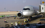 Saudi airport officials surround the first Qatar Airways plane in three years to land at King Khalid Airport in Riyadh, Saudi Arabia, Monday, Jan. 11, 2021. Saudi Arabia, along with the UAE, Bahrain and Egypt, ended a three-year dispute with Qatar following a Gulf Cooperation Council (GCC) summit in AlUla last week. (AP Photo/Amr Nabil)