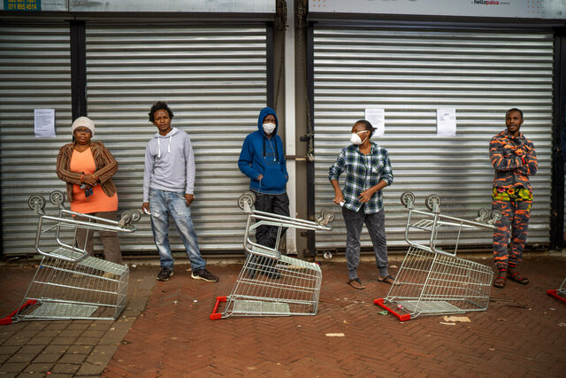 Residents of Yeoville neighborhood of Johannesburg, South Africa, wait in line to enter a grocery store Friday April 3, 2020. South Africa went into a nationwide lockdown for 21 days in an effort to control the spread of the coronavirus. The new coronavirus causes mild or moderate symptoms for most people, but for some, especially older adults and people with existing health problems, it can cause more severe illness or death.(AP Photo/Jerome Delay)