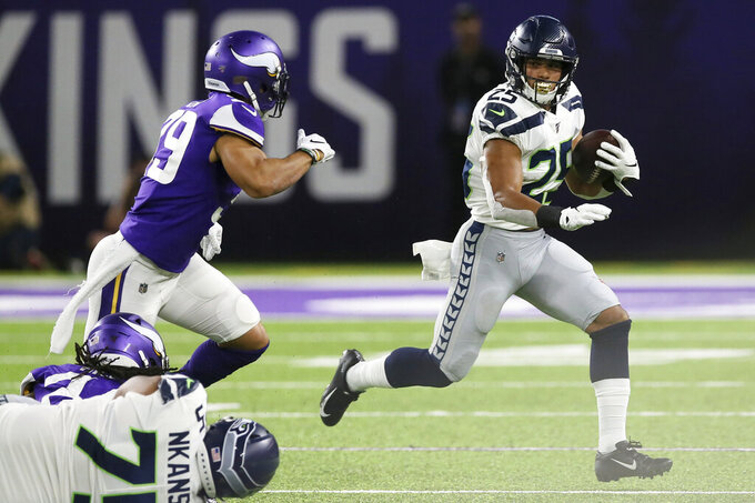 Seattle Seahawks running back Travis Homer (25) runs from Minnesota Vikings safety Marcus Epps, left, during the second half of an NFL preseason football game, Sunday, Aug. 18, 2019, in Minneapolis. (AP Photo/Jim Mone)