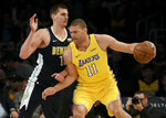 Los Angeles Lakers center Brook Lopez, right, posts up on Denver Nuggets center Nikola Jokic during the first half of an NBA basketball game in Los Angeles, Tuesday, March 13, 2018. (AP Photo/Kelvin Kuo)