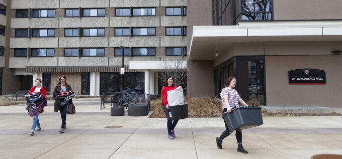 FILE - Calli Fiez, right, and her mother, Kim, carry her belongings to their car while moving out of Witte Residence Hall Thursday, March 12, 2020 on the campus of UW-Madison in Madison, Wis. A Republican state lawmaker plans to block the University of Wisconsin from instituting COVID-19 testing, masking and vaccination protocols on campuses across the state, a move that comes as health officials sound warnings about the rapidly spreading, highly contagious delta variant. (Mark Hoffman/Milwaukee Journal-Sentinel via AP, File)