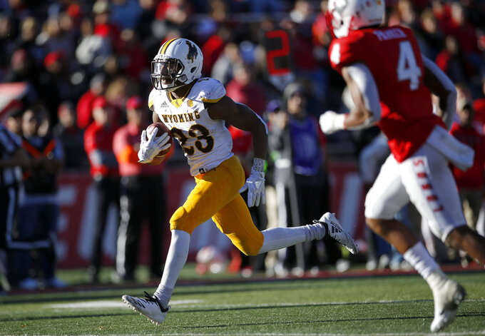 Wyoming running back Xazavian Valladay (23) sprints to the end zone to score a touchdown past New Mexico safety Bijon Parker (4) during the second half of an NCAA college football game in Albuquerque, N.M., Saturday, Nov. 24, 2018. Wyoming won 31-3. (AP Photo/Andres Leighton)
