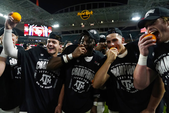 Texas A&M players celebrate after winning the Orange Bowl NCAA college football game Saturday, Jan. 2, 2021, in Miami Gardens, Fla. Texas A&M defeated North Carolina 41-27. (AP Photo/Lynne Sladky)