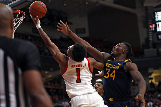 Texas Tech's Terrence Shannon Jr. (1) lays up the ball around West Virginia's Oscar Tshiebwe (34) during the first half of an NCAA college basketball game Wednesday, Jan. 29, 2020, in Lubbock, Texas. (AP Photo/Brad Tollefson)