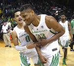Oregon's Will Richardson, left, congratulates Francis Okoro, center, with Victor Bailey Jr., right, after the team's 73-47 win over Arizona in an NCAA college basketball game Saturday, March 2, 2019, in Eugene, Ore. (AP Photo/Chris Pietsch)