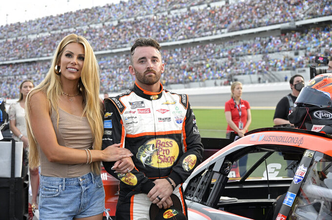 Austin Dillon stands next to his vehicle with his wife Whitney Dillon on pit road before a NASCAR Cup Series auto race at Daytona International Speedway, Saturday, Aug. 28, 2021, in Daytona Beach, Fla. (AP Photo/Phelan M. Ebenhack)