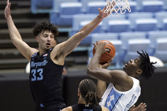Marquette forward Dawson Garcia (33) defends while North Carolina forward Day'Ron Sharpe (11) shoots during the first half of an NCAA college basketball game in Chapel Hill, N.C., Wednesday, Feb. 24, 2021. (AP Photo/Gerry Broome)