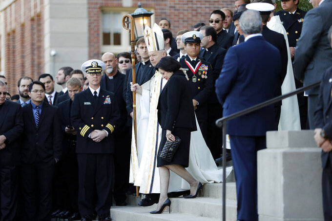 "FILE - In this March 21, 2018, file photo, Gayle Benson, widow of NFL New Orleans Saints and NBA New Orleans Pelicans owner Tom Benson, walks down the steps to receive his casket with New Orleans Archbishop Gregory Aymond for visitation at Notre Dame Seminary in New Orleans. Aymond, who knew the couple separately before they married in 2004, has become almost a part of the team, thought by some to bring the beloved Saints help from a higher power. Aymond was there to eulogize Tom Benson as a ""New Orleans saint on Earth"" and walk side by side with Gayle in the funeral procession. (AP Photo/Gerald Herbert, File)"