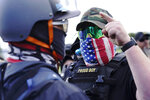 "FILE - In this Sept. 26, 2020 file photo, a right-wing demonstrator gestures toward a counter protester as members of the Proud Boys and other right-wing demonstrators rally in Portland, Ore. President Donald Trump didn't condemn white supremacist groups and their role in violence in some American cities this summer. Instead, he said the violence is a ""left-wing"