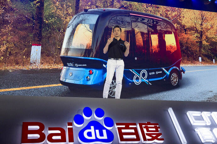 FILE - In this July 4, 2018, file photo, Robin Li, CEO of search giant Baidu, speaks near an image of the Apolong, China's first L4 fully autonomous bus, during the Baidu Create 2018 in Beijing, China. Geely said Monday, Jan. 11, 2021, it will form an electric car venture with tech giant Baidu, adding to a flurry of corporate tie-ups in the industry to share soaring technology development costs. (AP Photo/Ng Han Guan, File)