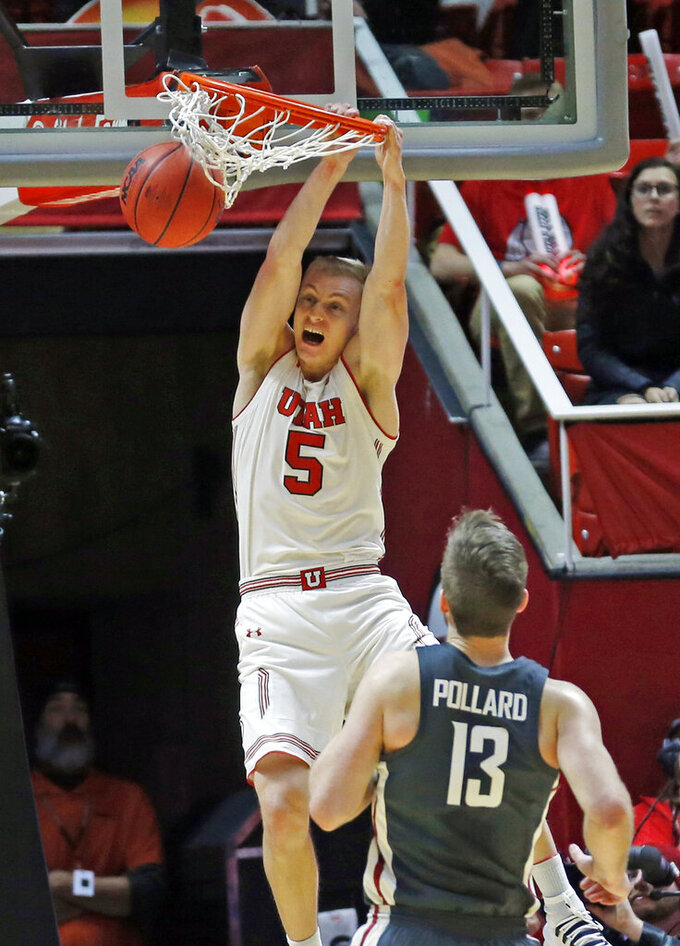 Utah guard Parker Van Dyke (5) dunks the ball as Washington State forward Jeff Pollard (13) looks on during the first half of an NCAA college basketball game Saturday, Jan. 12, 2019, in Salt Lake City. (AP Photo/Rick Bowmer)