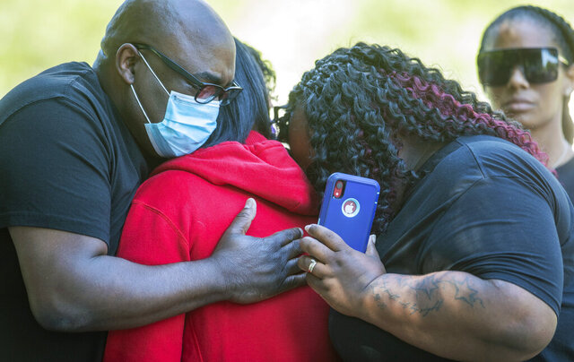 Family members hug during a press conference to announce federal charges on behalf of the family of Dreasjon Reed, Tuesday, June 16, 2020 in Indianapolis. Reed was fatally shot by an Indianapolis police officer. (Robert Scheer/The Indianapolis Star via AP)