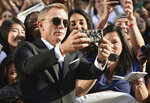 Daniel Craig takes a selfie with fans as he attends the premiere for