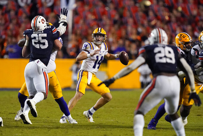 LSU quarterback Max Johnson (14) looks to pass under pressure from Auburn defensive end Colby Wooden (25) in the second half of an NCAA college football game in Baton Rouge, La., Saturday, Oct. 2, 2021. Auburn won 24-19. (AP Photo/Gerald Herbert)