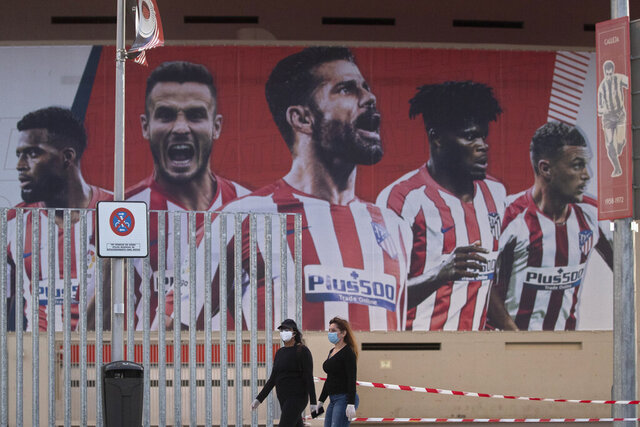 FILE - In this May 5, 2020 file photo, two women wearing face masks pass by a giant poster of Atletico Madrid soccer players at the Wanda Metropolitano stadium in Madrid, Spain. Two members of Atletico Madrid's group set to travel to Portugal for the Champions League quarterfinals have tested positive for the coronavirus on Sunday, Aug. 9. (AP Photo/Paul White, File)