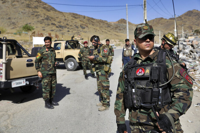 Afghan special forces stand guard at the site of a suicide car bomb explosion that killed at least four people, on the outskirts of Kabul, Afghanistan, Thursday, Sept. 12, 2019. Taliban spokesman Zabihullah Mujahid has claimed responsibility for the bombing in a statement sent to the media. (AP Photo/Ebrahim Noroozi)
