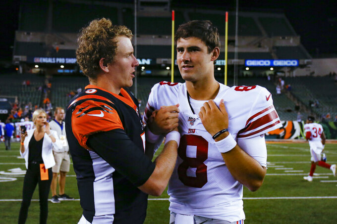Cincinnati Bengals quarterback Ryan Finley (5) meets with New York Giants quarterback Daniel Jones (8) after an NFL preseason football game Thursday, Aug. 22, 2019, in Cincinnati. (AP Photo/Gary Landers)